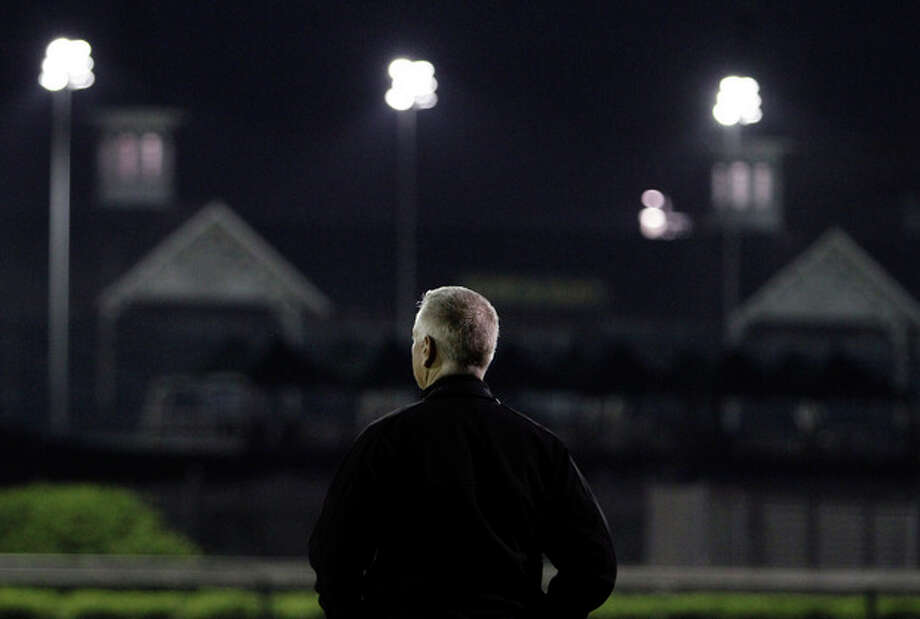 Trainer Todd Pletcher watches morning workouts at Churchill Downs Wednesday, May 1, 2013, in Louisville, Ky. (AP Photo/Garry Jones) / FR50389 AP
