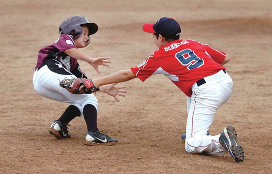 Hour Photo/Alex von KleydorffCranbury's Jake Caviccihia, left, gets tagged out by Norwalk's Joey Benincaso at third base during game four of the 2012 Kinlock Tournament at Devine Field in Norwalk. Cranbury won, 7-6. / 2012 The Hour Newspapers