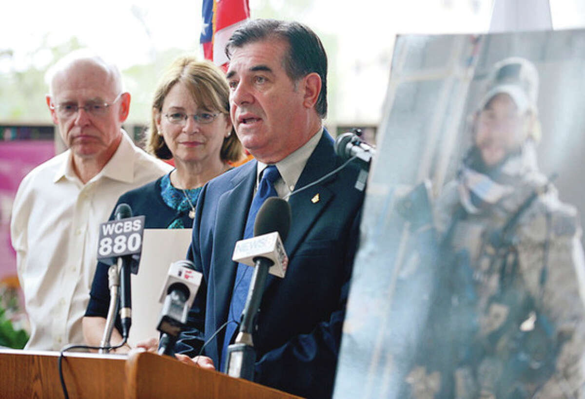 Hour photos / Erik Trautmann Stamford Mayor Michael Pavia speaks during a press conference Wednesday to mark the one-year anniversary of Chief Petty Officer Brian Bill's death in Afghanistan. Bill's parents, Mike and Pat Perry, look on.