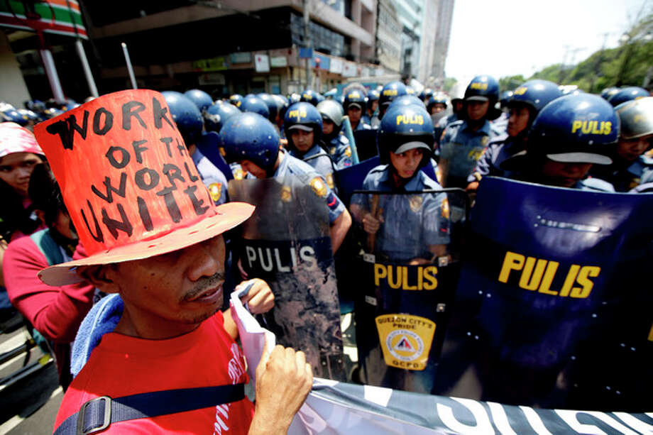 "Riot police block protesters as they try to march towards U.S. Embassy in Manila to mark International Labor Day Wednesday May 1, 2013 in Manila, Philippines. The workers, who have demanding wage increases for years, assailed President Aquino III for his Labor Day ""gift"" of non-wage benefits. The protesters have been clamoring for years for a P125-Peso ($3.125) across-the-board wage hike and condemn the Government's policy of outsourcing labor which allegedly eliminates job security. (AP Photo/Bullit Marquez) / AP"