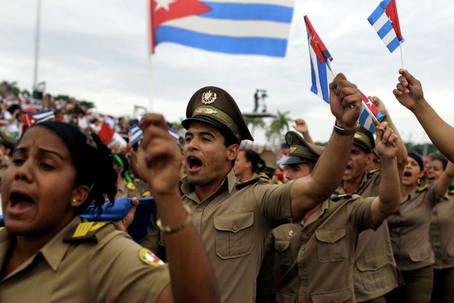 Soldiers shout revolutionary slogans and carry Cuban flags during the annual May Day march in Revolution Square in Havana, Cuba, Wednesday, May 1, 2013. Workers held protests, parades, strikes and other demonstrations in cities across the world on Wednesday. (AP Photo/Franklin Reyes) / AP