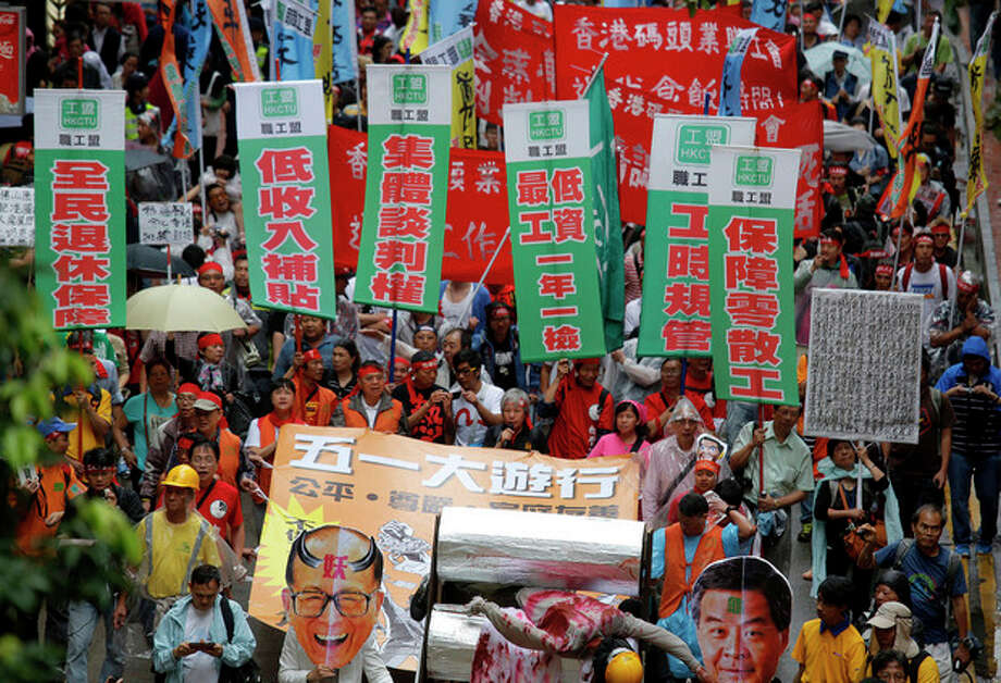 "Workers and protesters holding a defaced portrait of Hong Kong billionaire Li Ka-shing and banners reading ""right of collective negotiation,"" ""low pay subsidy"" and ""retire security"" march to the government's office during a May Day rally in Hong Kong Wednesday, May 1, 2013. Hundreds of workers, local labor rights groups and striking dockworkers joined the annual May Day rally in Hong Kong to fight for better wages and working conditions. (AP Photo/Vincent Yu) / AP"