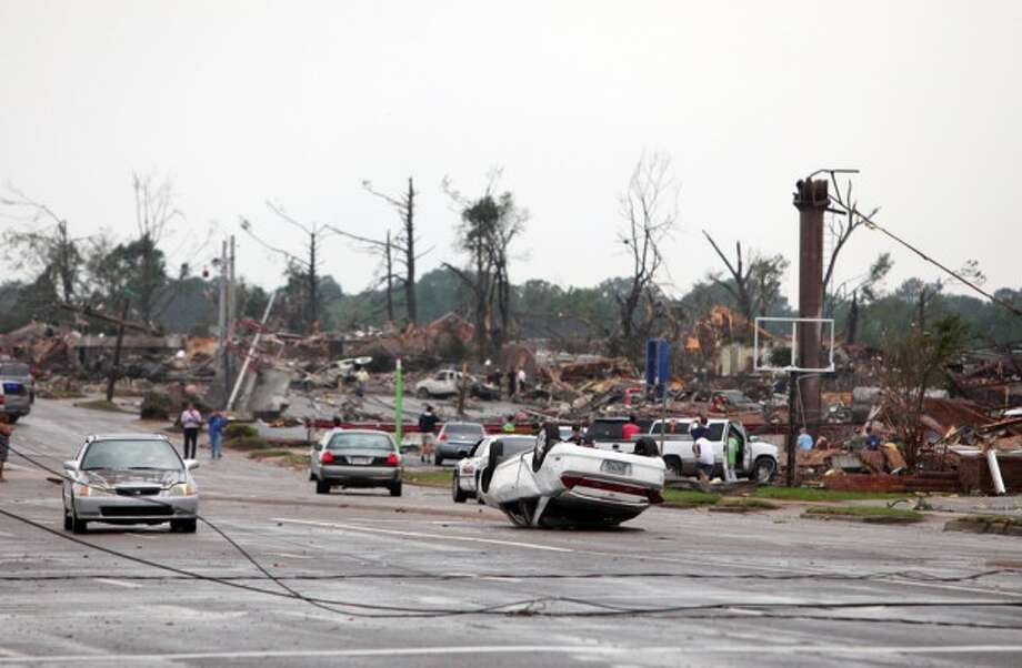 Cars are flipped and buildings are destroyed along 15th St. and the surrounding neighborhoods in Tuscaloosa, Ala. Wednesday, April 27, 2011. A wave of severe storms laced with tornadoes strafed the South on Wednesday, killing at least 16 people around the region and splintering buildings across swaths of an Alabama university town. (AP Photo/The Tuscaloosa News, Dusty Compton)
