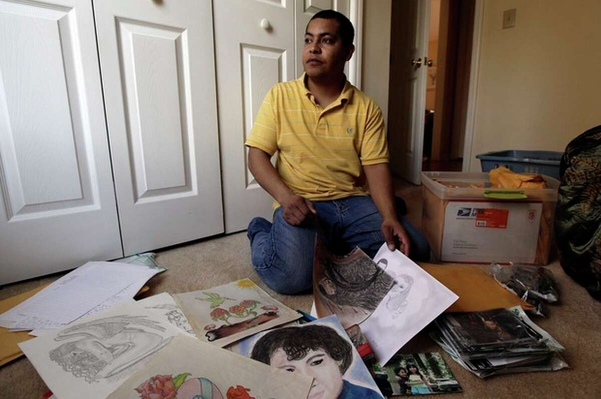 In a photo made Friday, Jan. 27, 2012 in Durham, N.C., Pedro Guzman looks through items he made and collected while incarcerated. U.S. Immigration and Customs Enforcement detained the Guatemalan native in 2009, and he spent 19 months in private prisons run by CCA in Gainesville and Lumpkin, Georgia. Guzman was released and granted legal permanent residency in May, when ICE's Board of Immigration Appeals overturned his deportation order. (AP Photo/Gerry Broome)