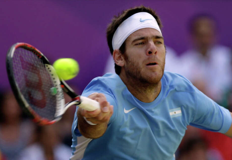 Juan Martin del Potro of Argentina returns to Roger Federer of Switzerland at the All England Lawn Tennis Club in Wimbledon, London at the 2012 Summer Olympics, Friday, Aug. 3, 2012. (AP Photo/Elise Amendola) / AP