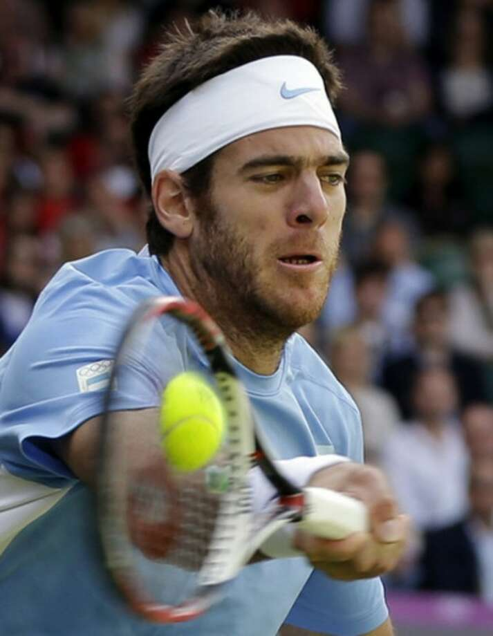 Juan Martin del Potro of Argentina returns to Roger Federer of Switzerland at the All England Lawn Tennis Club in Wimbledon, London at the 2012 Summer Olympics, Friday, Aug. 3, 2012. (AP Photo/Elise Amendola)
