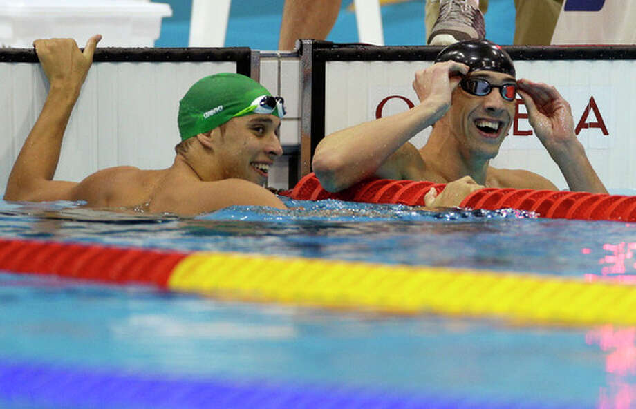 United States' Michael Phelps, right, and South Africa's Chad le Clos react to their scores in the men's 100-meter butterfly swimming final at the Aquatics Centre in the Olympic Park during the 2012 Summer Olympics in London, Friday, Aug. 3, 2012. Phelps won a gold medal in the event, le Clos won a silver medal. (AP Photo/Michael Sohn) / AP
