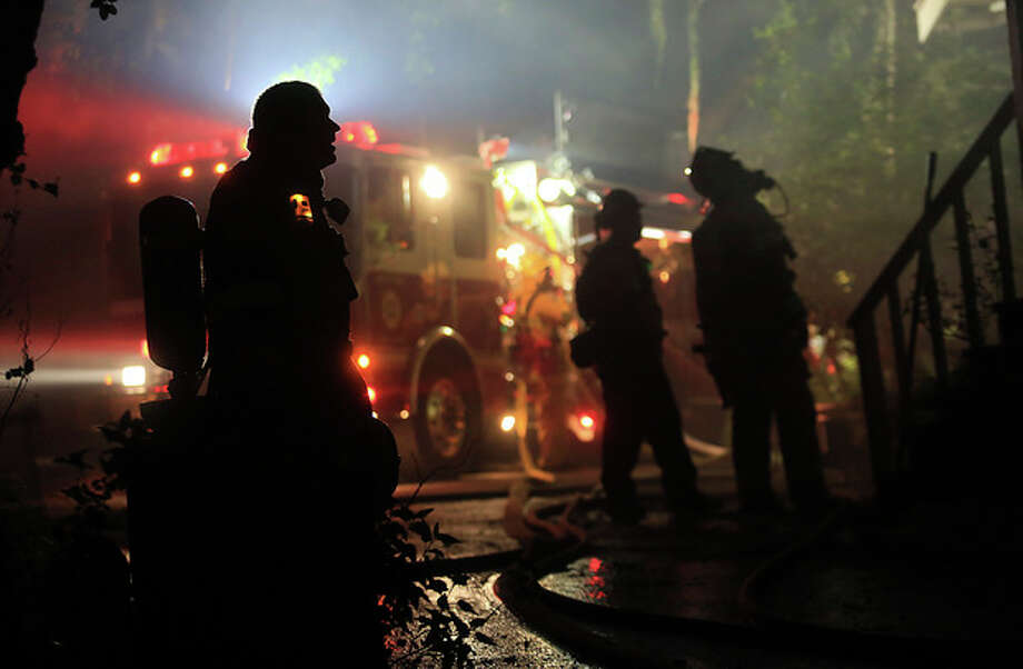 Fire crews respond to a wind driven vegetation fire that damaged this home on Highway 128 early Wednesday May 1, 2013 in Knights Valley, Calif. Crews battled two small wildfires on Wednesday in California wine country that were pushed by gusty winds. (AP Photo/The Press Democrat, Kent Porter) / The Press Democrat