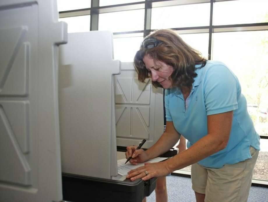 Eileen Nolan votes on the town budget at Wilton High School Saturday. Hour Photo / Danielle Robinson