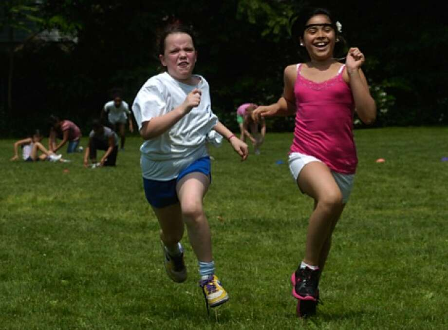 Fourth graders Laura Gallagher and Jocelyn Benitez race to the finish in the Find Your Sneaker event during the Kendall Elementary School Field Day Wedenesday. Hour photo / Erik trautmann