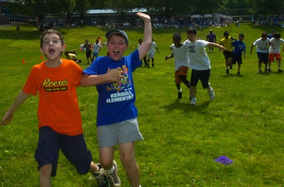 Fourth graders Ryan Pellini and Andrew Thompson celebrate their win in the Three Legged Race event during the Kendall Elementary School Field Day Wedenesday. Hour photo / Erik trautmann