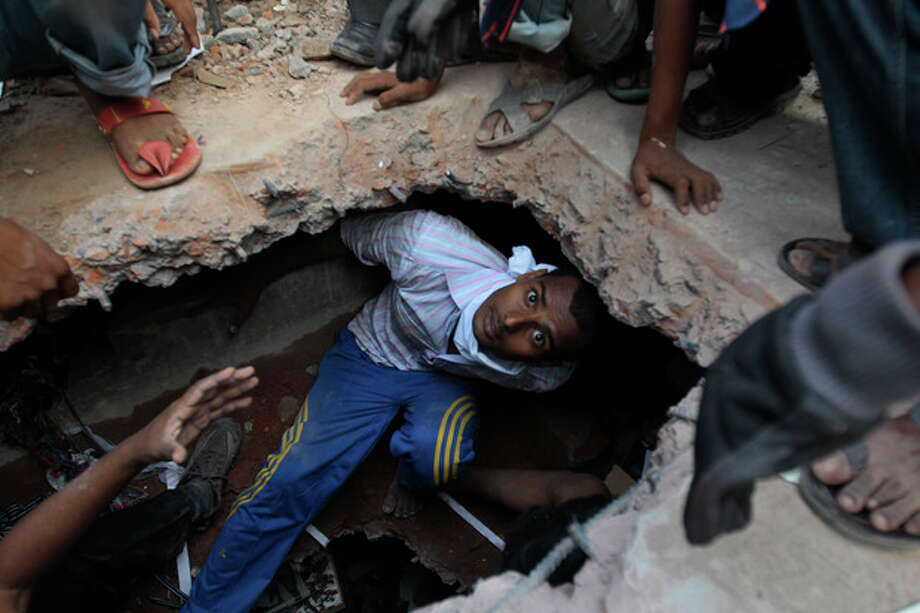 A Bangladeshi rescuer looking for survivors emerges from beneath a concrete slab of a building that collapsed Wednesday in Savar, near Dhaka, Bangladesh,Thursday, April 25, 2013. By Thursday, the death toll reached at least 194 people as rescuers continued to search for injured and missing, after a huge section of an eight-story building that housed several garment factories splintered into a pile of concrete on Wednesday. (AP Photo/A.M.Ahad) / AP