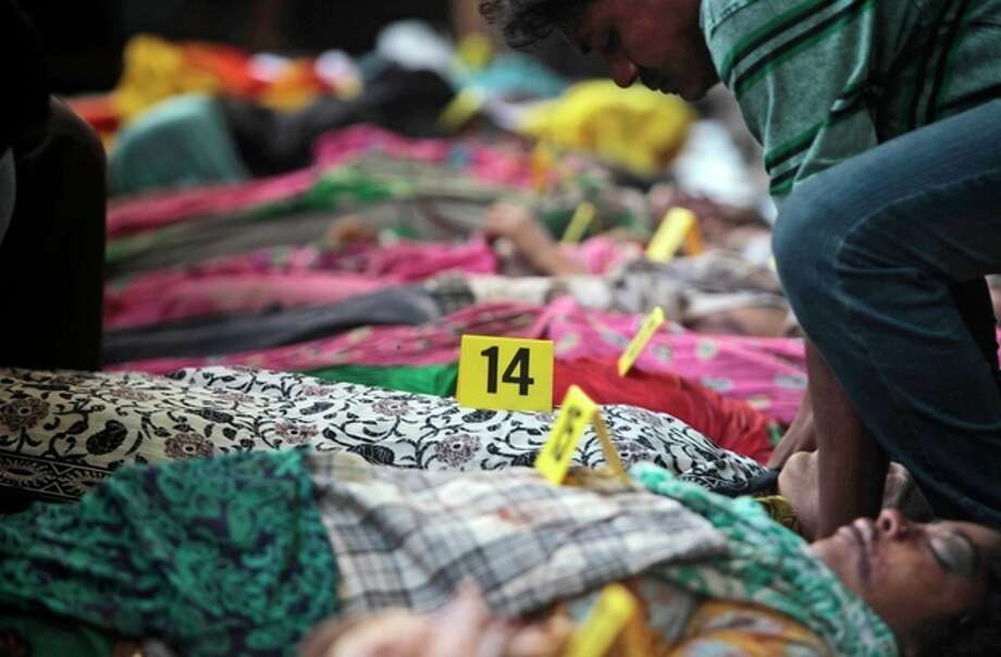 Bodies of victims of a building collapse lie numbered in a row in Savar, near Dhaka, Bangladesh, Wednesday, April 24, 2013. An eight-story building housing several garment factories collapsed near Bangladesh's capital on Wednesday, killing dozens of people and trapping many more under a jumbled mess of concrete. Rescuers tried to cut through the debris with earthmovers, drilling machines and their bare hands. (AP Photo/A.M.Ahad) / AP