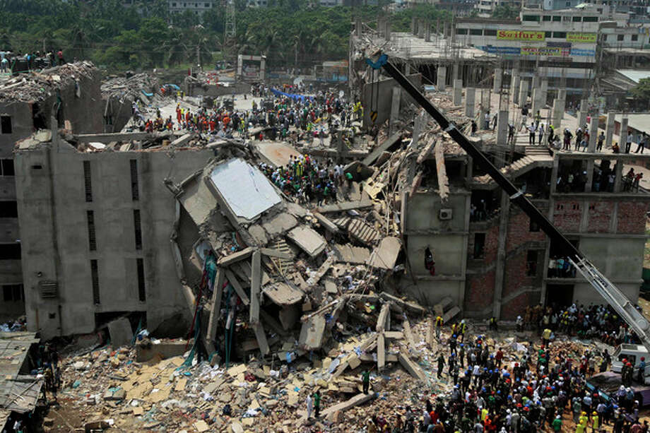 Bangladesh rescuers look for survivors and victims at the site of a building that collapsed Wednesday in Savar, near Dhaka, Bangladesh,Thursday, April 25, 2013. By Thursday, the death toll reached at least 194 people as rescuers continued to search for injured and missing, after a huge section of an eight-story building that housed several garment factories splintered into a pile of concrete. (AP Photo/A.M.Ahad) / AP