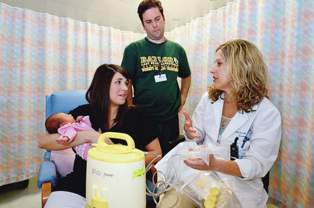 Hour photo / Erik Trautmann Mallory and Jon Green consult with patient educator Beth Innocenti about breastfeeding after Mallory Green gave birth to her daughter, Elise, at Norwalk Hospital.