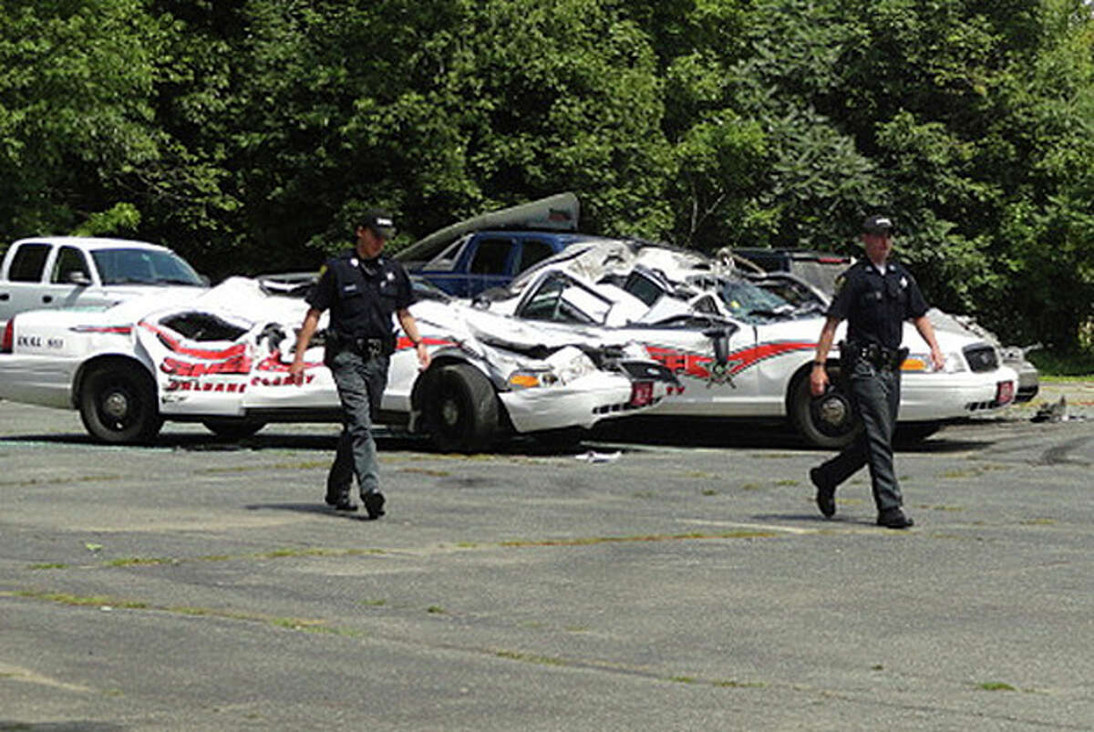 Sheriff officers walk past crushed cruisers at the Orleans County Sheriff's Department in Newport, Vt., Thursday, Aug. 2, 2012. Authorities say 34-year old Vermont farmer Roger Pion, angry over a recent arrest last month on charges of resisting arrest and marijuana possession, used a large tractor like a monster truck, destroying seven police cruisers. (AP Photo/Northland Journal, Scott Wheeler)