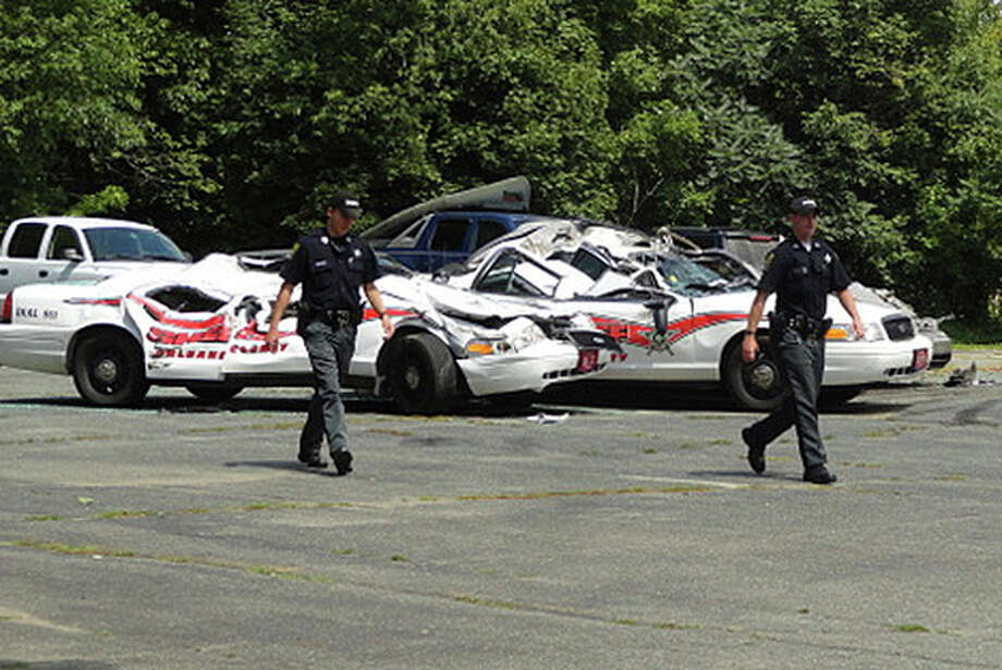Sheriff officers walk past crushed cruisers at the Orleans County Sheriff's Department in Newport, Vt., Thursday, Aug. 2, 2012. Authorities say 34-year old Vermont farmer Roger Pion, angry over a recent arrest last month on charges of resisting arrest and marijuana possession, used a large tractor like a monster truck, destroying seven police cruisers. (AP Photo/Northland Journal, Scott Wheeler) / Northland Journal