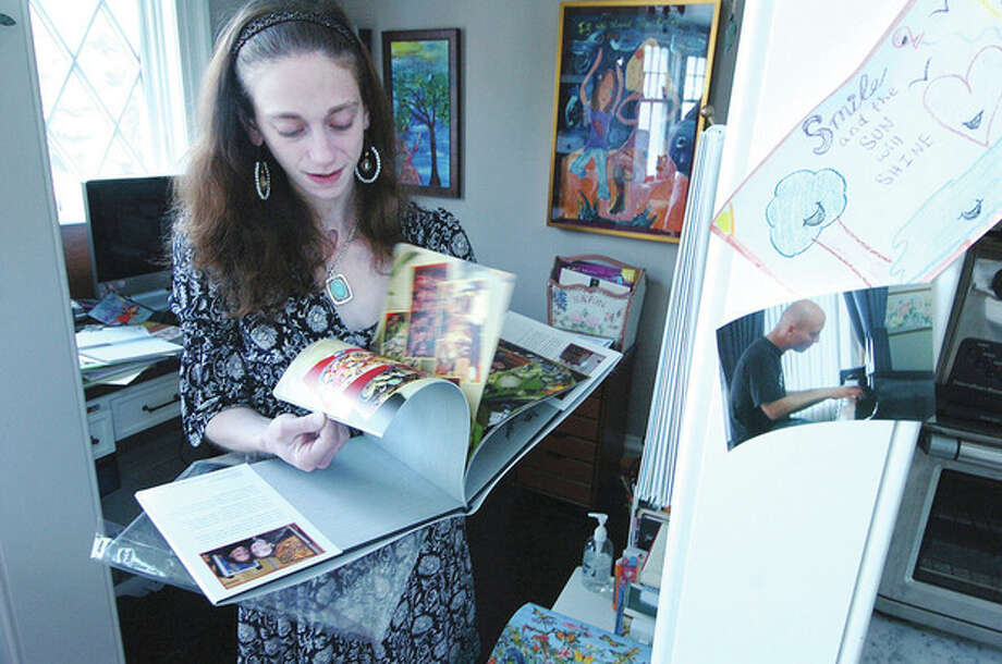 "Hour Photo/ Alex von Kleydorff. Amy Oestricher flips through her book about her art show, ""Journey into Daylight"" / 2012 The Hour Newspapers"
