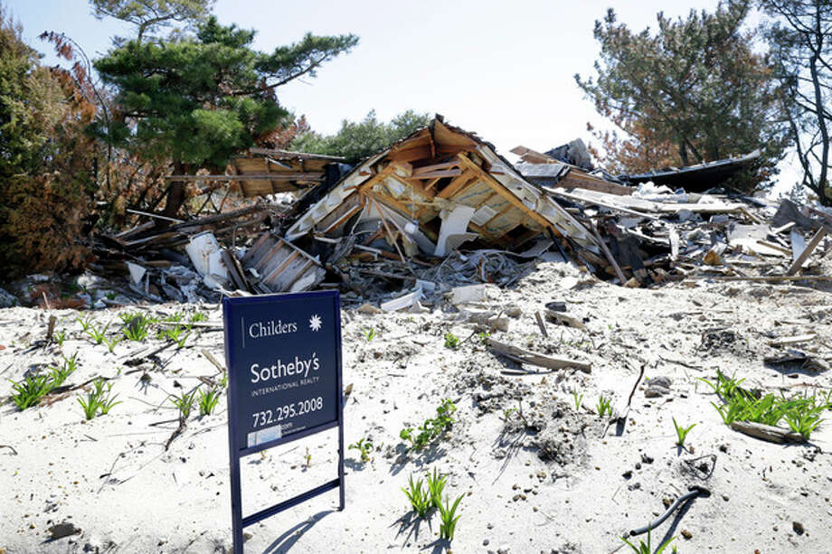 A realty sign stands Thursday, April 25, 2013, in Mantoloking, N.J., on a lot where the home was destroyed last October by Superstorm Sandy. Six months after Sandy devastated the Jersey shore and New York City and pounded coastal areas of New England, the region is dealing with a slow and frustrating, yet often hopeful, recovery. (AP Photo/Mel Evans) / AP