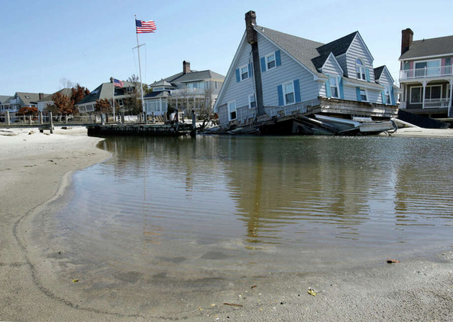 A home rests in Barnegat Bay, Thursday, April 25, 2013, in Mantoloking, N.J., after it was swept away last October by Superstorm Sandy. Six months after Sandy devastated the Jersey shore and New York City and pounded coastal areas of New England, the region is dealing with a slow and frustrating, yet often hopeful, recovery. (AP Photo/Mel Evans) / AP