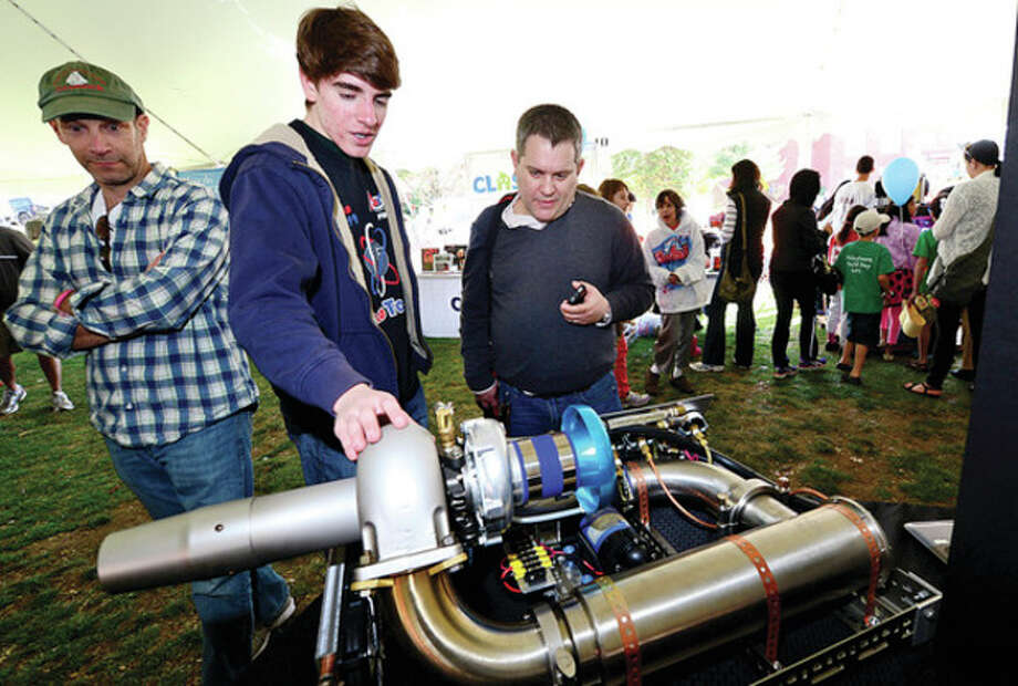 Hour photos / Erik TrautmannAbove, Chris Tomko shows Westport author and lecturer Alec Foege the jet engine Tomko designed and built at his home during the Westport Mini Maker Faire at Jesup Geen Saturday, a showcase of invention, creativity and resourcefulness, where people from tech enthusiasts to crafters to homesteaders to scientists to garage tinkerers show what they are making, and share what they are learning. Below right, Abby Connolly and Olivia Liebler try their hand at Makey Makey Ping Pong. Below left, Allison Herman of Compuchild Technology Education shows Neil Komma, 9, a Lego robot. / (C)2013, The Hour Newspapers, all rights reserved