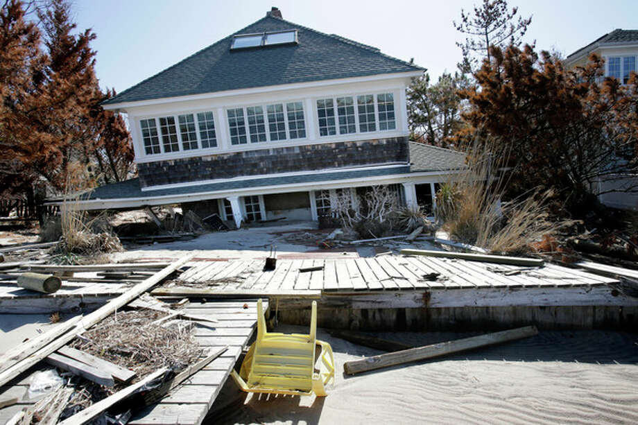 A home rests along Barnegat Bay, Thursday, April 25, 2013, in Mantoloking, N.J., after it was severely damaged last October by Superstorm Sandy. Six months after Sandy devastated the Jersey shore and New York City and pounded coastal areas of New England, the region is dealing with a slow and frustrating, yet often hopeful, recovery. (AP Photo/Mel Evans) / AP