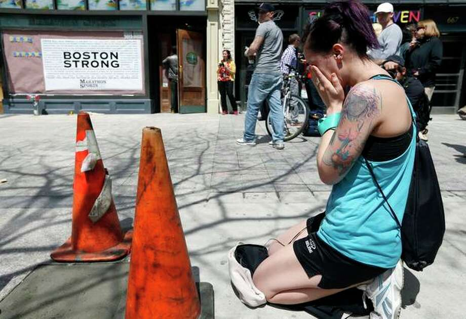Hillary Branyik, of Boston, kneels at the site where the first bomb detonated on April 15 near the finish line of the Boston Marathon on Boylston Street in Boston, Wednesday, April 24, 2013. Traffic was allowed to flow all the way down Boylston Street on Wednesday morning for the first time since two explosions on April 15. (AP Photo/Michael Dwyer) / AP