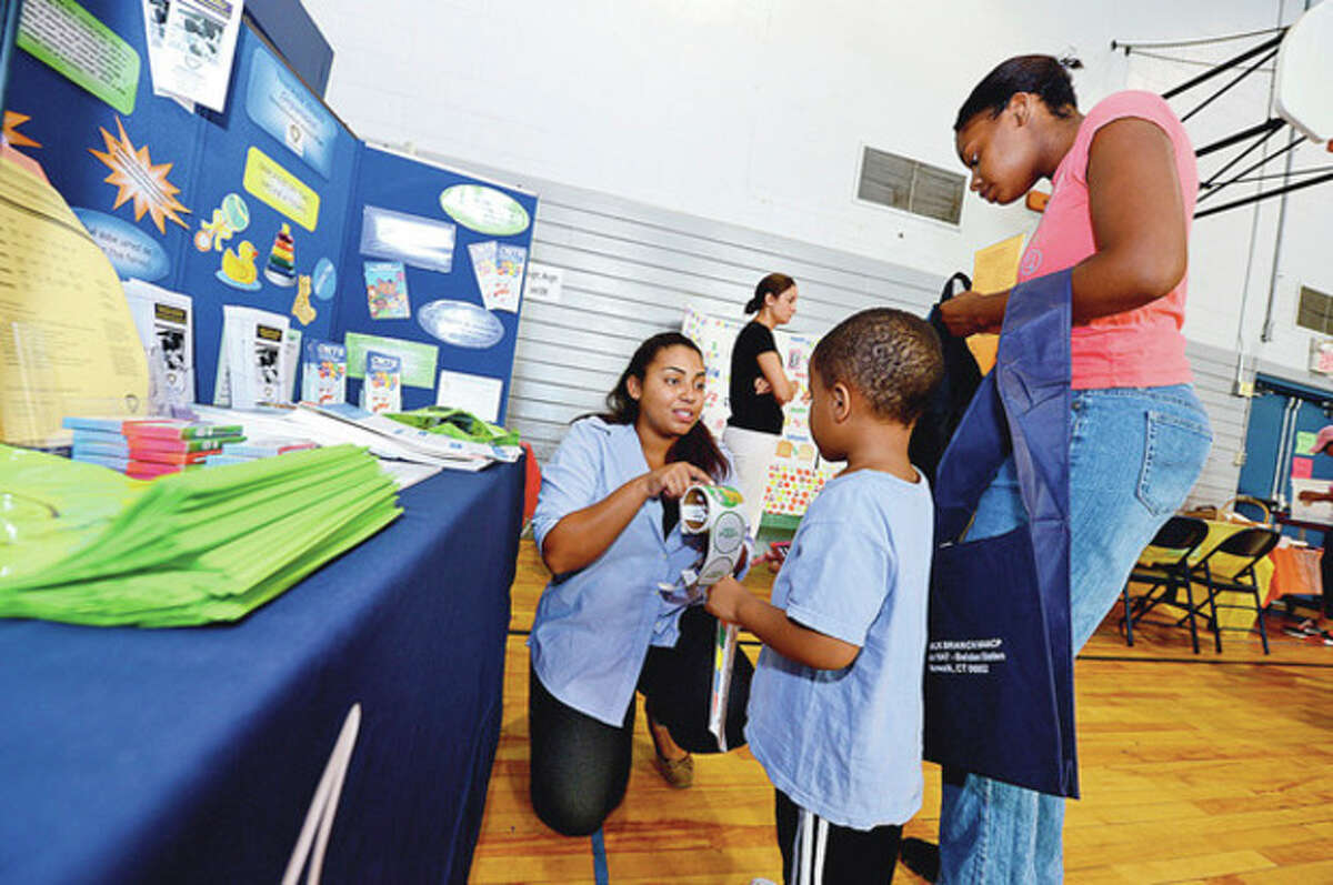 Hour photos / Erik Trautmann Norwalk Health Department employee China Perez-Brown helps Jahmar and Angela Butler during the Community Health Fair at Nathaniel Ely School Saturday. Among the free health options were free blood pressure testing, mammograms and cholesterol tests.