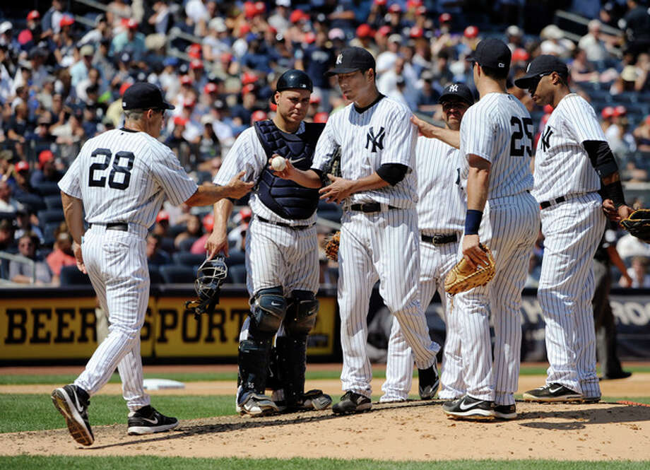 New York Yankees manager Joe Girardi takes starting pitcher Hiroki Kuroda out of the baseball game after he hit Seattle Mariners' Brendan Ryan in the arm with a pitch in the seventh inning, Saturday, Aug. 4, 2012, at Yankee Stadium in New York. The Mariners won 1-0. (AP Photo/Kathy Kmonicek) / FR170189 AP