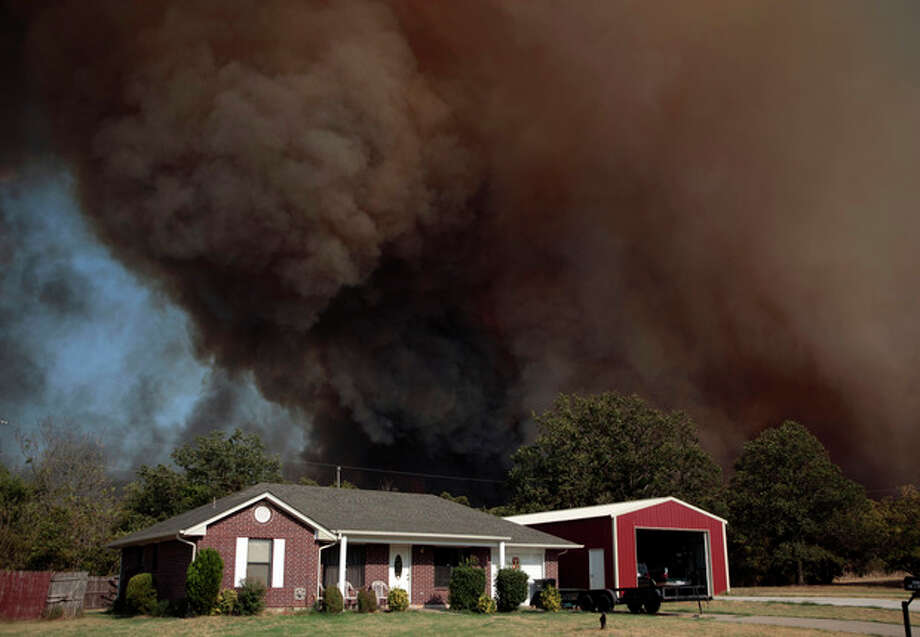 A smoke surrounds home during a large wildfire Friday, Aug. 3, 2012 in Luther, Okla. A wildfire whipped by gusty, southerly winds swept through rural woodlands north and south of Oklahoma City on Friday, burning several homes as firefighters struggled to contain it in 113-degree heat. (AP Photo/The Oklahoman, Sarah Phipps) TABLOIDS OUT / The Oklahoman