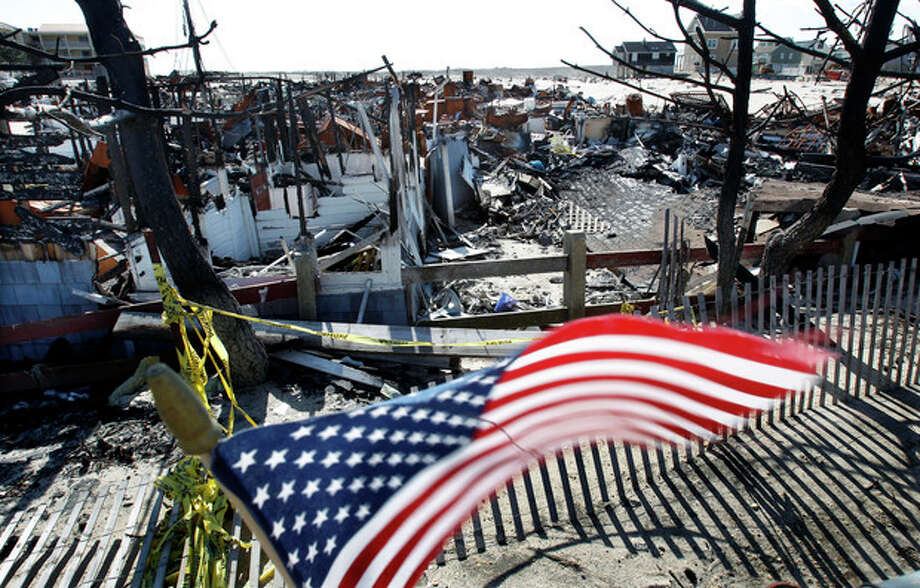 Flags decorate a fence Thursday, April 25, 2013, in Brick, N.J., around the burned remains of more than 60 small bungalows at Camp Osborn which were destroyed last October during Superstorm Sandy. Six months after Sandy devastated the Jersey shore and New York City and pounded coastal areas of New England, the region is dealing with a slow and frustrating, yet often hopeful, recovery. (AP Photo/Mel Evans) / AP