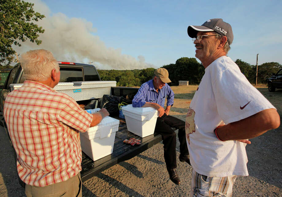 From left, Gayland Cannon, Eugene Hacker and Ron Ross wait at a gas station at SE108 and Hwy 9 after evacuating their homes in the area of SE 132nd and Cedar Lane as a wildfire burns through Cleveland County near Norman, Okla., Friday, Aug. 3, 2012. A wildfire stirred by high winds sweeping through rural woodlands just south of the Oklahoma City area has set at a number of homes on fire. (AP Photo/The Oklahoman, Nate Billings) TABLOIDS OUT / THE OKLAHOMAN