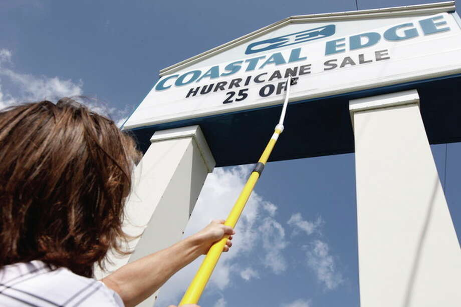 Chris Galiffa, who works at a surf clothing and accessory shop, announces a sale on their sign board in anticipation of the arrival of Hurricane Irene in Kill Devil Hills, N.C., Thursday, Aug. 25, 2011 on North Carolina's Outer Banks. (AP Photo/Charles Dharapak) / AP