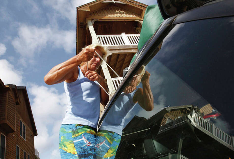 A vacationer who did not want to be identified ties luggage to the roof of her car as she heeds a mandatory visitor evacuation as Hurricane Irene approaches in Nags Head, N.C., Thursday, Aug. 25, 2011, in North Carolina's Outer Banks. A hurricane watch was issued early Thursday for much of the North Carolina coast. (AP Photo/Charles Dharapak) / AP