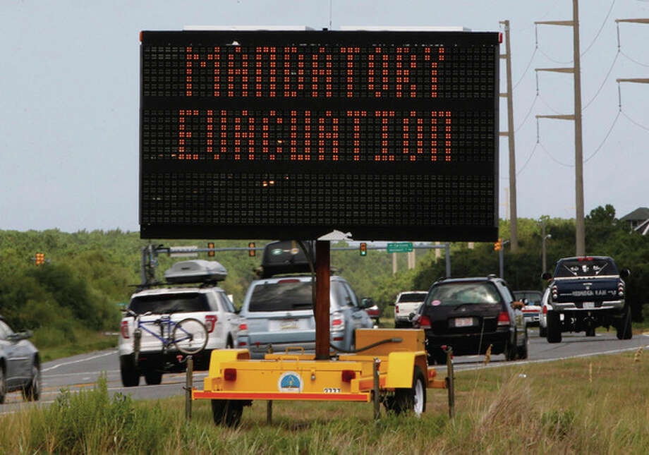 A sign declaring a mandatory evacuation in anticipation of the arrival of Hurricane Irene is seen as motorists head north in Nags Head, N.C., Thursday, Aug. 25, 2011 on North Carolina's Outer Banks. (AP Photo/Charles Dharapak) / AP