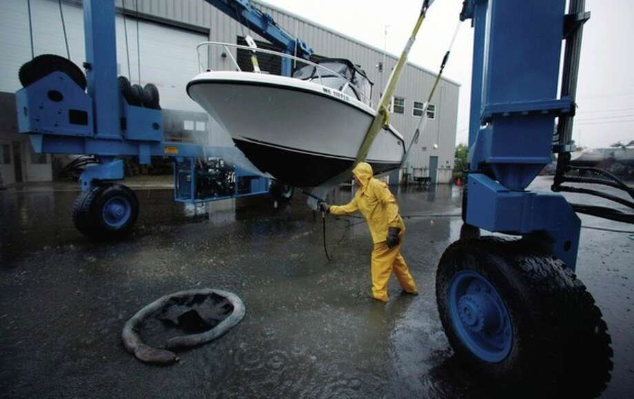 Peter Gavett pressure washes the hull of a pleasure boat he hauled out of the water at Brewer Marine as a precaution before the arrival of Hurricane Irene, Thursday, Aug. 25, 2011, in Freeport, Maine. The Maine Emergency Management Agency urged boaters were to secure their vessels, and the state's lobstermen began moving their fishing gear farther offshore to avoid damage. (AP Photo/Robert F. Bukaty) / AP