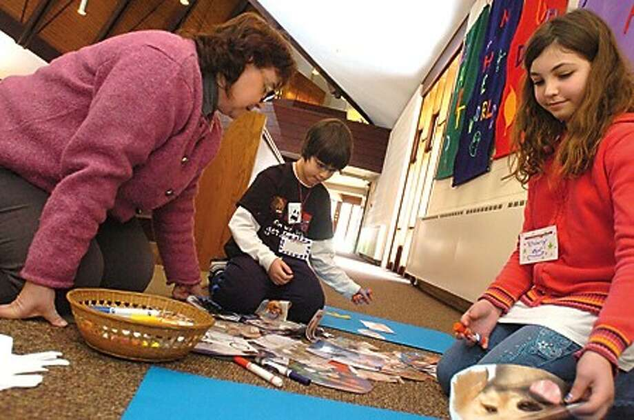 """Linda Snyder, Missioner of Christian Formation for Children with the Episcopal Diocese of Connecticut makes crafts with Jason Bilgrei 9 and his sister and Kimberly Bilgrei 11 at the Church of Christ The Healer in Stamford Sunday at the first """"Worship for the Wiggly"""" church service for special needs children. hour photo/matthew vinci"""
