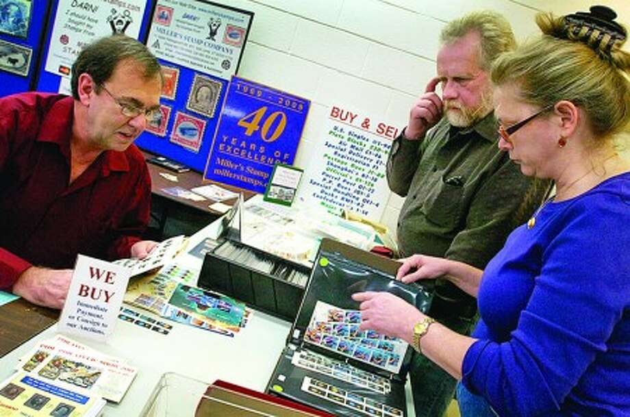 Members of the Norwalk Stamp Club, Bonnie Adams and Brian O''Neill, right, looks over stamps for sale from Irving Miller at the stamp club''s show Saturday at the Norwalk Senior Center. Hour photo / Erik Trautmann