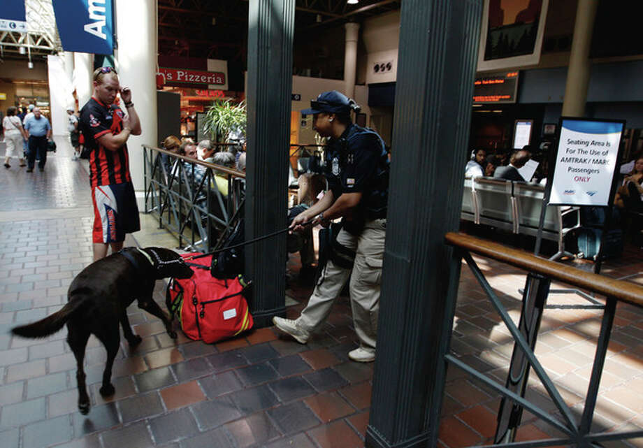 An Amtrak police officer checks the bag of a passenger at Union Station on Saturday, Sept. 10, 2011, ahead of the 10th anniversary Sunday of the Sept. 11 attacks. (AP Photo/Jose Luis Magana) / FR159526 AP