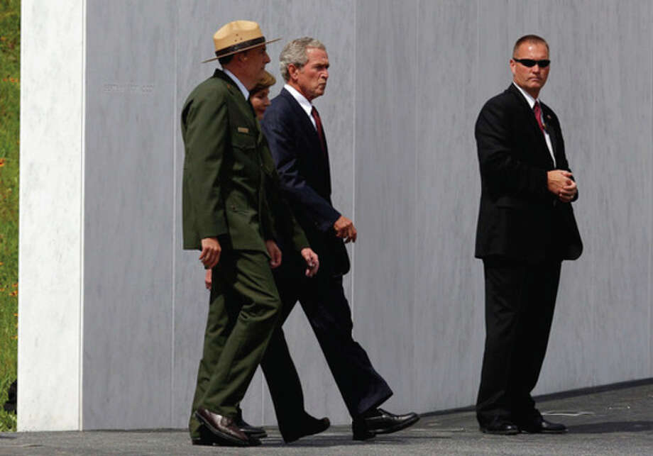 Former President George W. Bush and former first lady Laura Bush, obscured, pass the Wall of Names as they are escorted to the stage at the dedication of phase 1 of the permanent Flight 93 National Memorial near the Sept. 11 crash site of Flight 93 in Shanksville, Pa. Saturday Sept. 10, 2011. (AP Photo/Amy Sancetta) / AP