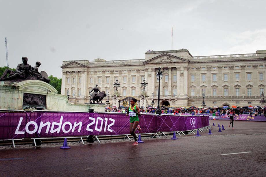 Ethiopia's gold medal winner Tiki Gelana runs in front of Buckingham Palace during women's marathon at the 2012 Summer Olympics on, Sunday, Aug. 5, 2011 in London. (AP Photo/Daniel Ochoa de Olza) / AP