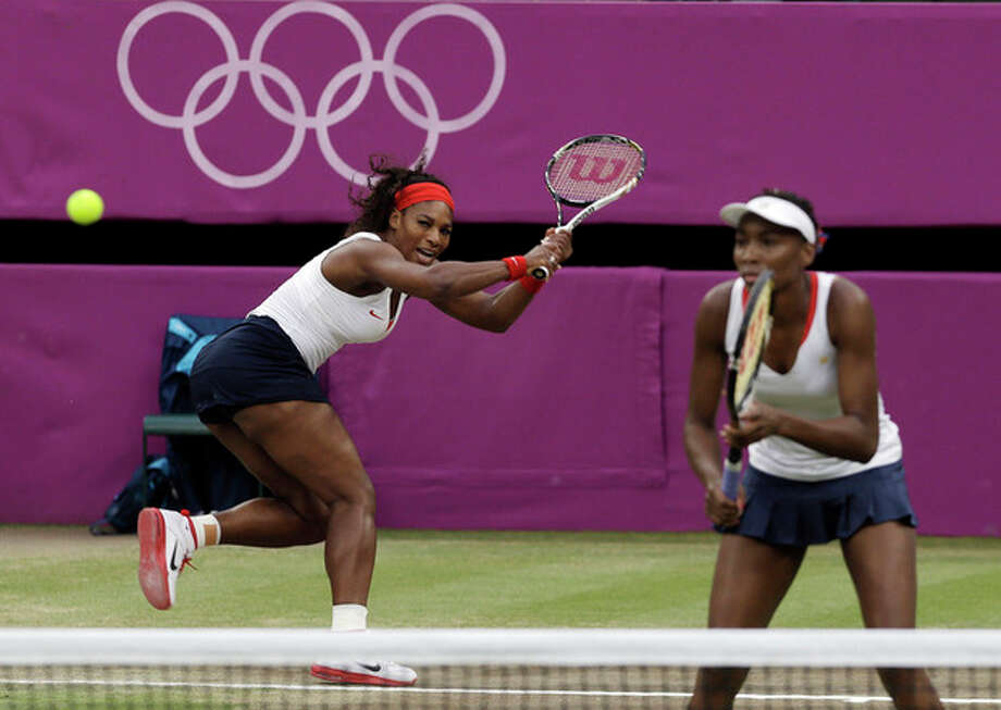 Serena Williams, left, and Venus Williams of the United States compete against Andrea Hlavackova and Lucie Hradecka of the Czech Republic during the gold medal women's doubles match at the All England Lawn Tennis Club in Wimbledon, London at the 2012 Summer Olympics, Sunday, Aug. 5, 2012. (AP Photo/Elise Amendola) / AP