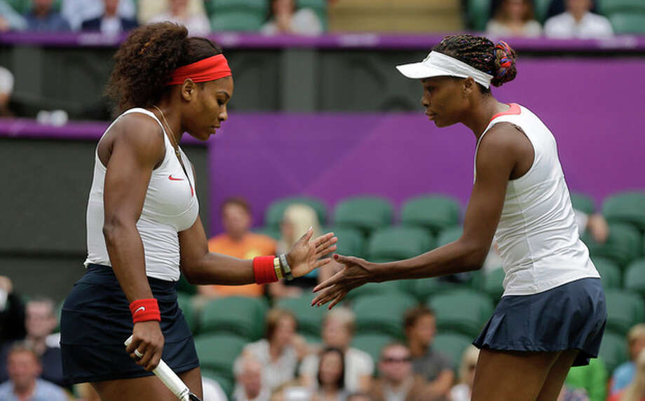 United States' Serena Williams, left, reacts with partner Venus Williams, right, as they play against Czech Republic's Lucie Hradecka and Andrea Hlavackova in a women's doubles gold medal tennis match at the All England Lawn Tennis Club at Wimbledon, in London, at the 2012 Summer Olympics, Sunday, Aug. 5, 2012. (AP Photo/Victor R. Caivano) / AP