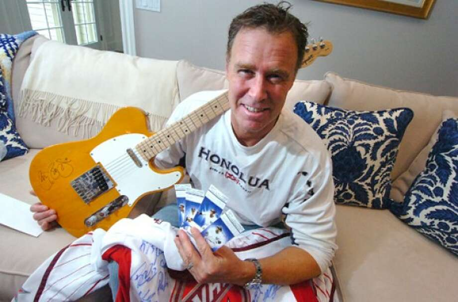 Photo/Alex von Kleydorff. Ian O''Malley holds just a few of the auction and raffle items like an autographed Bon Jovi guitar, an NHL All Star game autographed by both teams jersey and 4 field level Yankees tickets.