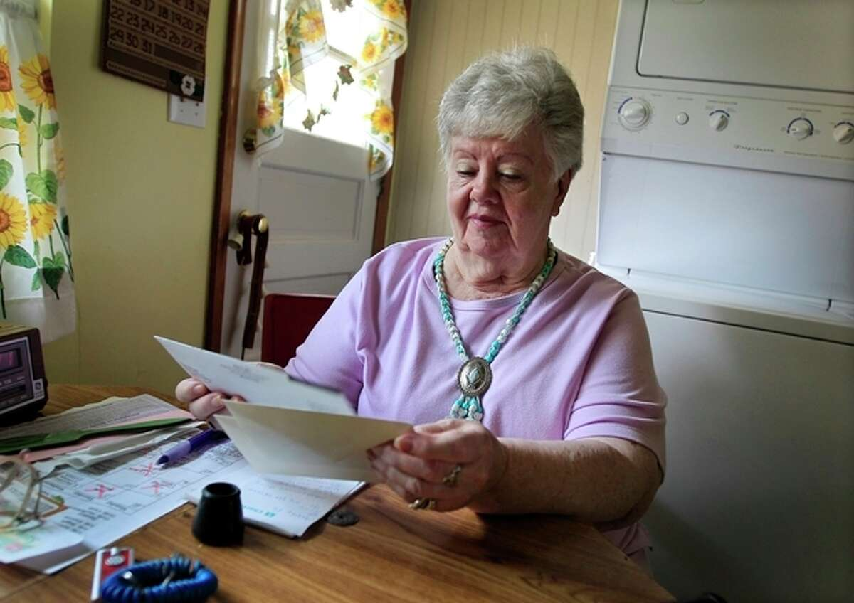 """In this July 26, 2012, photo, Neta Homier looks over bills in her home in Toledo, Ohio. Homier says she relies on Social Security to pay her bills and while she is confident the program will continue to help her she fears it will not be able to rely on it. """"Social Security is what?'s carrying me,"""" Homier said. """"It pays all my bills."""" People retiring today are part of the first generation of workers who have paid more in Social Security taxes during their careers than they will receive in benefits after they retire. It?'s a historic shift that will only get worse for future retirees, according to an analysis by The Associated Press. Previous generations got a much better bargain, mainly because payroll taxes were very low when Social Security was enacted in the 1930s and remained so for decades. (AP Photo/Carlos Osorio)"""