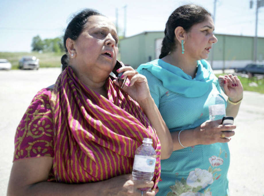 Parminder Kaleka, left, who said her brother-in-law was in the Sikh temple on S. Howell Ave. in Oak Creek, Mich. where a shooting occured, uses a phone to try to get more information on Sunday, Aug. 5, 2012. (AP Photo/Milwaukee Journal-Sentinel, Mike De Sisti) / Milwaukee Journal-Sentinel