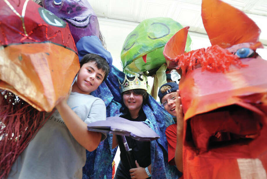 Hour photos / Matthew VinciFrom left, Trevor McGee 10, Gavin McGee 12 and John Miller 13 get ready to march in the SoNo Arts Celebration Puppet Parade on Sunday.