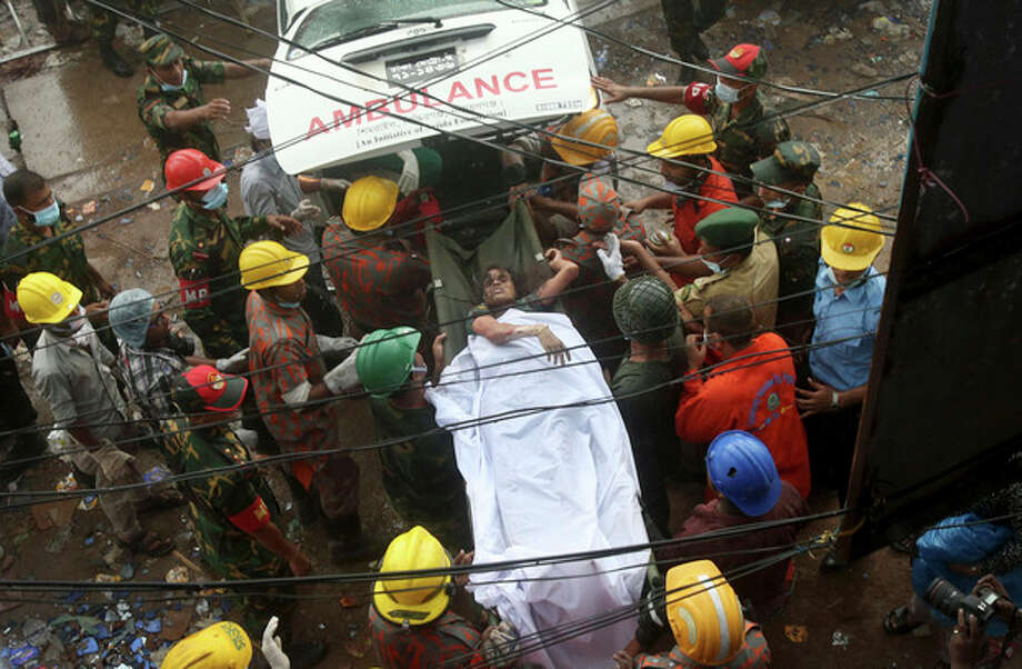 A survivor is carried on a stretcher into a waiting ambulance after being evacuated from a garment factory building that collapsed Wednesday in Savar, near Dhaka, Bangladesh, Saturday, April 27, 2013. Police in Bangladesh took five people into custody in connection with the collapse of a shoddily-constructed building this week, as rescue workers pulled 19 survivors out of the rubble on Saturday and vowed to continue as long as necessary to find others despite fading hopes.(AP Photo/Wong Maye-E) / AP