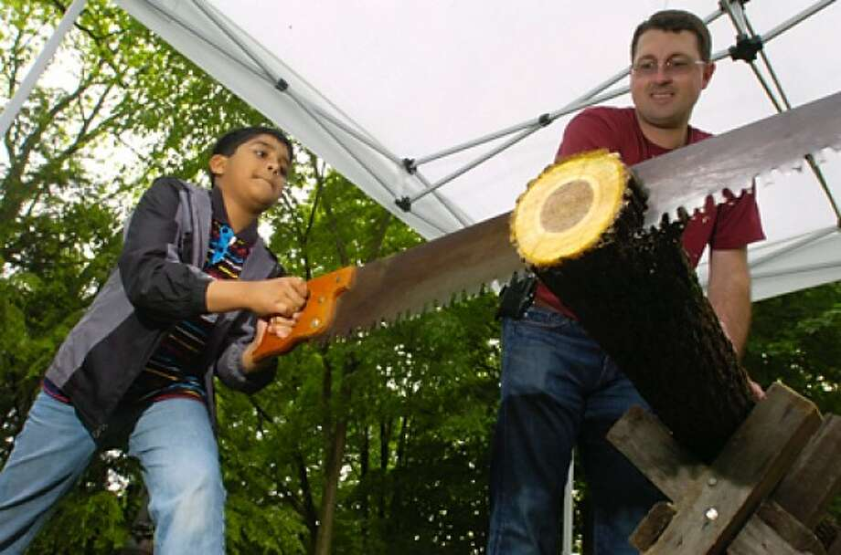 Cider Mill Elementary School 4th grader Purab Angruji saws wood while school volunteer Aaron Masek looks on during a visit to the Wilton Historical Society where the students learned about life in colonial times Tuesday. Hour photo / Erik Trautmann