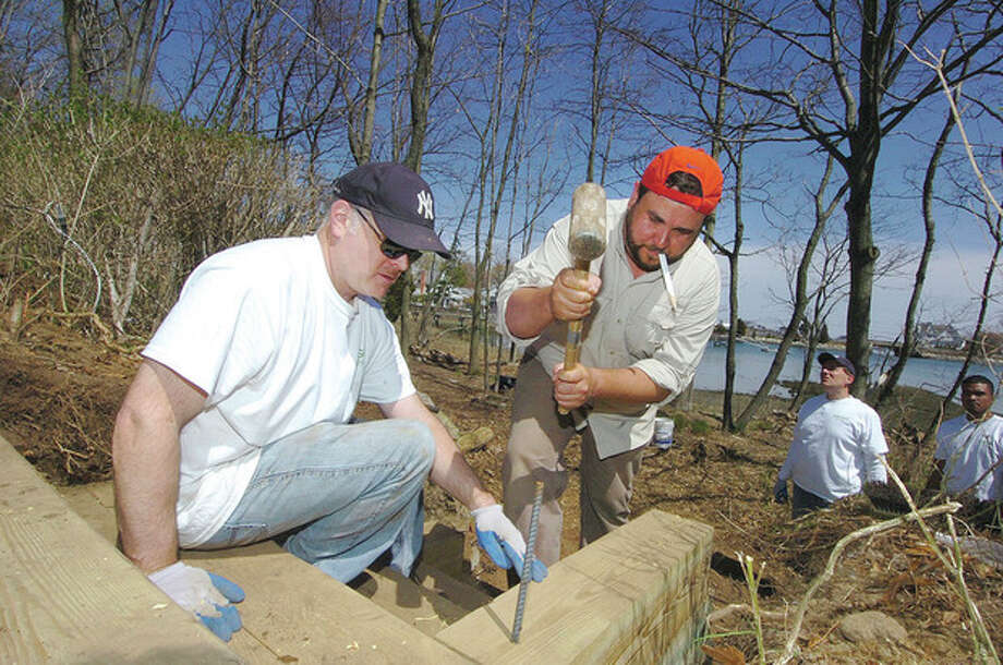 Hour Photo / Alex von KleydorffDiageo's Mark Collinge steadies a stair as Scott Sattler hammers a section of Rebar through the edge to anchor step 7 of 8 that are being built to provide access to one of the trails at Farm Creek Preserve in Rowayton. / 2013 The Hour Newspapers
